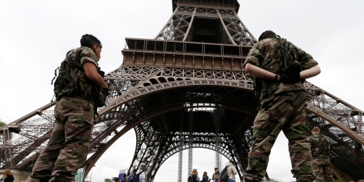 Soldiers stand by tourists as they patrol near the Eiffel Tower in Paris