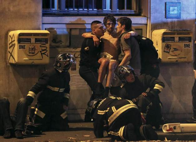 ATTENTION EDITORS - VISUAL COVERAGE OF SCENES OF INJURY OR DEATH French fire brigade members aid an injured individual near the Bataclan concert hall following fatal shootings in Paris, France, November 13, 2015. At least 30 people were killed in attacks in Paris and a hostage situation was under way at a concert hall in the French capital, French media reported on Friday. REUTERS/Christian Hartmann TPX IMAGES OF THE DAY