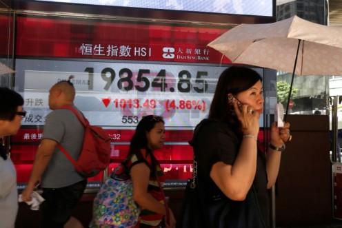 People walk past panel displaying falling Hang Seng Index in Hong Kong