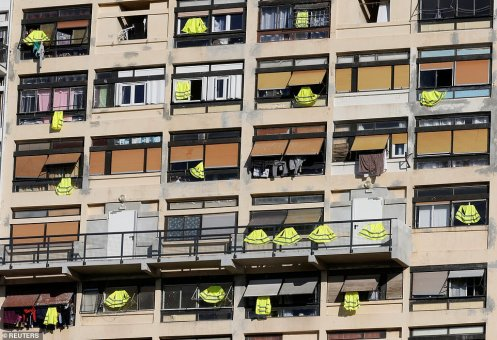 7133354-6470897-Yellow_vests_are_hung_outside_windows_of_an_apartment_building_i-a-17_1544186347947