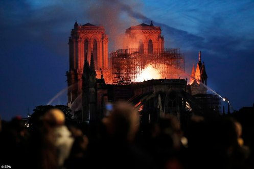 12312844-6925015-People_watch_in_Paris_this_evening_as_the_fire_at_the_Notre_Dame-a-270_1555359017581
